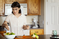 Woman seasoning salad while standing at kitchen in home - CAVF12278