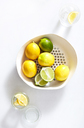 Overhead view of lemons in container over white background - CAVF12335