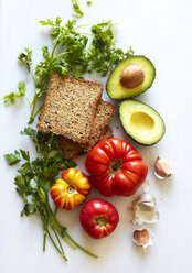 Overhead view of bread, avocado and vegetables over white background - CAVF12344
