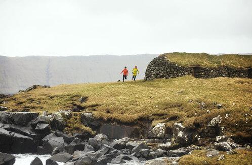 Friends jogging on field against rocky coastline - CAVF12353