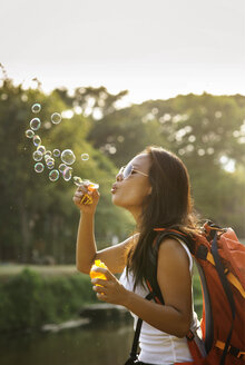 Playful woman blowing bubbles against sky on sunny day - CAVF12365