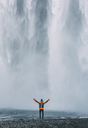 Man standing with arms outstretched against Skogafoss waterfall at Iceland - CAVF12386