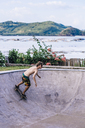 Young man skateboarding in concrete pool - CAVF12407