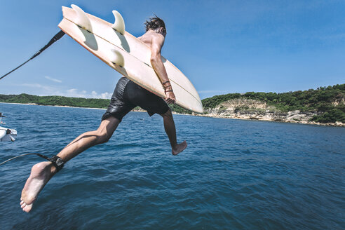 Man with surfboard jumping into sea against sky during sunny day - CAVF12419