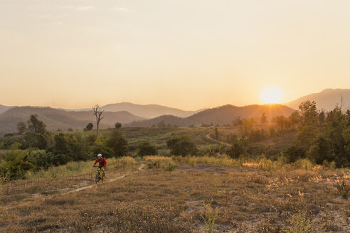 High angle view of man riding mountain bike on field against sky during sunset - CAVF12425