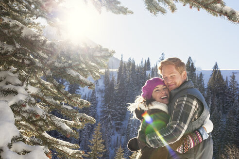 Couple embracing while standing in snowy forest against clear sky - CAVF12479