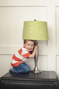Portrait of boy holding and playing with lamp shade on table - CAVF12485