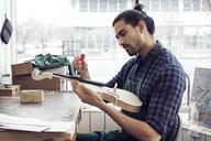 Instrument maker working on violin in workshop - CAVF12503