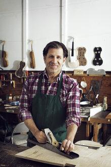 Portrait of worker standing in violin workshop - CAVF12506