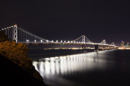 Illuminated Oakland Bay Bridge over sea against sky at night - CAVF12560
