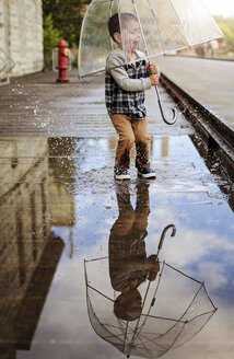 Playful boy with umbrella jumping on puddle at street - CAVF12614