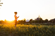 Side view of sportswoman using smart phone while standing at grassy field against clear sky during sunset - CAVF12635