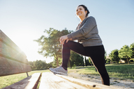 Low angle view of happy woman stretching legs on bench while standing against clear sky at park - CAVF12662