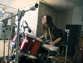 Cheerful woman enjoying while playing drum kit at home - CAVF12869
