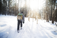 Rear view of male hiker with backpack walking in snow covered forest on sunny day - CAVF12884