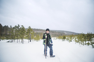 Portrait of boy holding stick while standing on snow covered field against clear sky - CAVF12893