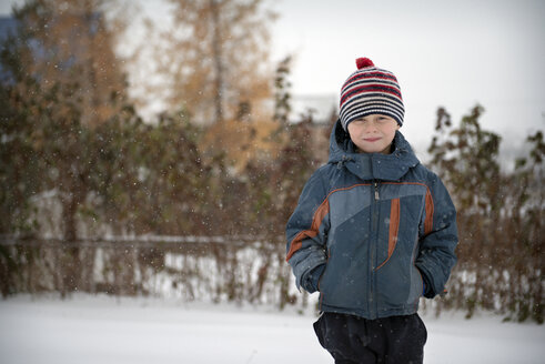 Portrait of smiling boy in warm clothing standing on snow covered field - CAVF12998