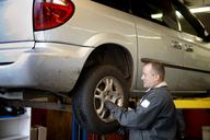 Mechanic examining car tire at auto repair shop - CAVF13154