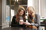 Happy friends using phone while sitting at sidewalk cafe - CAVF13184