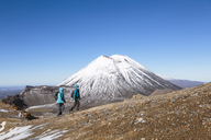 Female friends hiking at Mt Ngauruhoe against clear blue sky on sunny day - CAVF13316