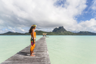 Woman in traditional clothing standing on jetty over lagoon against cloudy sky - CAVF13346