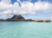 Stilt houses in lagoon of Bora Bora island against cloudy sky - CAVF13349