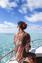 Rear view of woman looking at view while traveling on boat against cloudy sky - CAVF13376