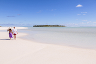 Rear view of couple walking at beach against blue sky during sunny day - CAVF13385