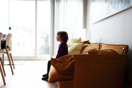 Side view of girl looking away while relaxing on sofa at home - CAVF13577