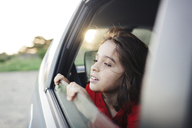 Smiling boy looking through window while traveling in car - CAVF13661
