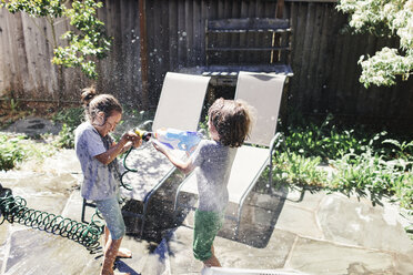 High angle view of brothers playing with water in yard during sunny day - CAVF13673
