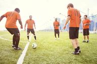 Sportsmen playing soccer on field - CAVF13685