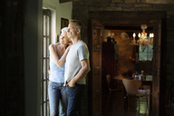 Senior couple looking through window while standing at home - CAVF13712