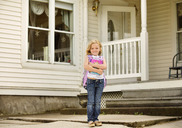 Portrait of happy girl holding books while standing outside house - CAVF13754