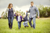 Happy children with parents enjoying on grassy field - CAVF13766