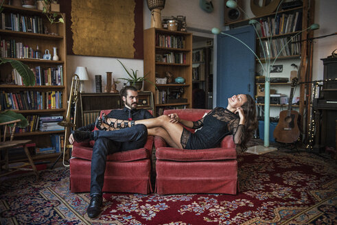 Young couple relaxing on sofa at home - CAVF13955