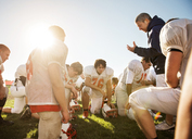 Confident coach giving training to players on American football field on sunny day - CAVF14009