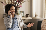 Happy woman talking on smart phone at home - CAVF14093