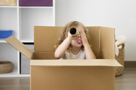 Playful girl looking through cardboard tube while sitting in box - CAVF14267