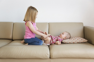 Happy girl playing with sister lying on sofa at home - CAVF14312