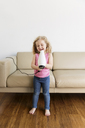 Happy girl singing into hair dryer while standing on hardwood floor by sofa at home - CAVF14327
