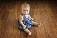 High angle portrait of baby girl sitting on floor at home - CAVF14333