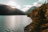Scenic view of mountains by lake on sunny day - CAVF14366
