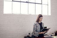 Confident businesswoman reading diary while standing against window at office - CAVF14411