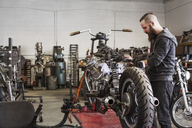 Serious mechanic working on motorcycle at repair shop - CAVF14423