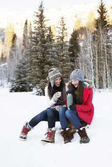 Cheerful family holding coffee while sitting on rock in snowy field - CAVF14477