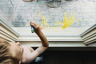 Overhead view of shirtless boy writing on window at home - CAVF14501