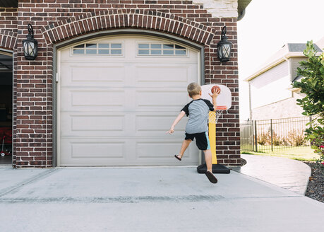 Rear view of boy playing basketball on driveway - CAVF14513