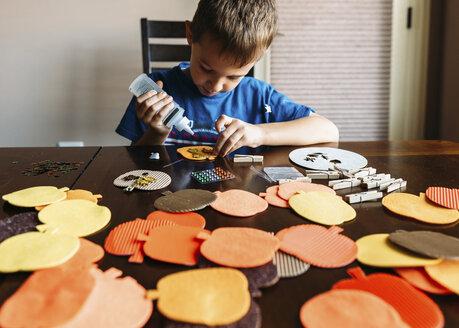 Boy making apples shape art at home - CAVF14546