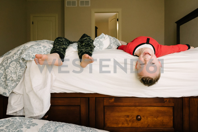 Happy siblings playing on bed at home - CAVF14552